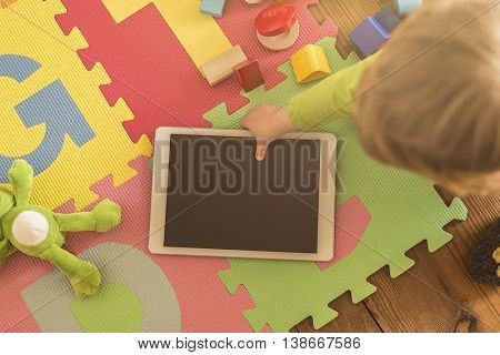 top view of a toddler grabbing a tablet device from its playground