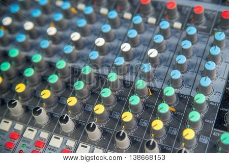 Close-up detail on the dials of an audio mixing console in a recording studio. Music industry concept.
