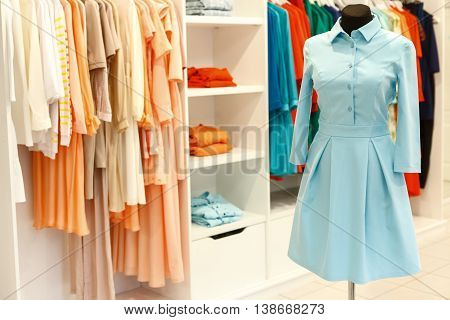 Fashionable designer dress on mannequin near clothes on hangers in boutique