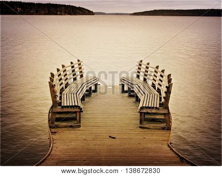 Two inward facing benches on the edge of a lake.