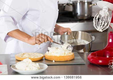 Chef decorating a delicious cake with cream