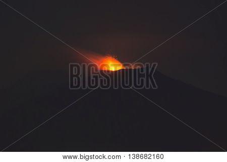 Eruption of Sicilian volcano Etna at night seen from Taormina at 15 kilometre away.