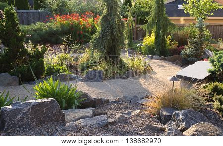 A curved path winds through this backyard perennial garden in the late afternoon sun.