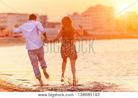 Rear view of happy couple running in summer on the beach in a tropical place. Two lovers in vacation in an idyllic nature scene sharing positive feelings and emotions. Magic moments of loving hearts.