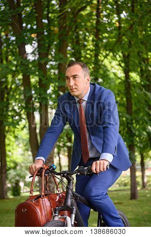 Successful businessman is riding a bicycle in park. He is carrying bag and wearing suit. Worker is looking forward with aspiration