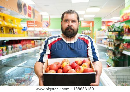 Big man in the store bought a lot of apples in a box