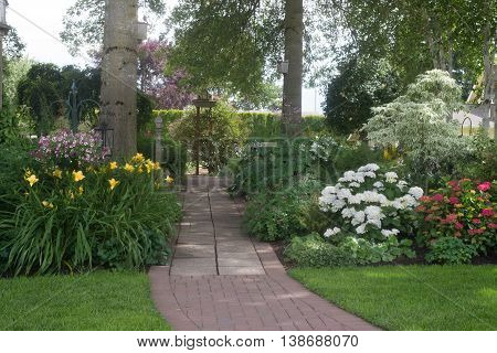 A beautifully designed brick walkway leads into a back yard perennial garden.