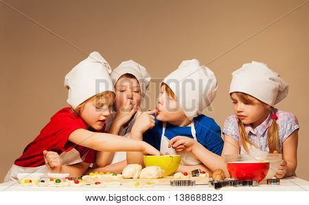 Four cute kids, boys and girl in baker's uniform tasting dough for handmade cookies, licking their fingers