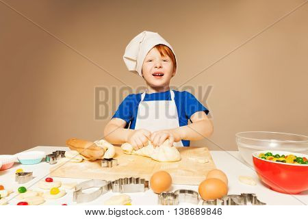 Cute baker, redheaded kid boy in cook's uniform kneading dough for candy filled cookies, background with copy-space