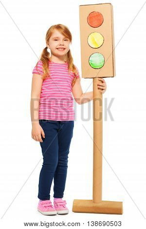 Full-length portrait of smiling girl with pig-tails, standing near handmade cardboard traffic light, isolated on white