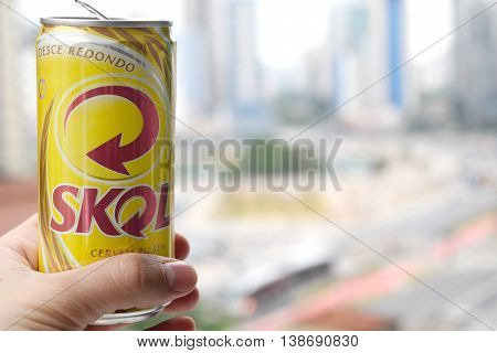 SAO PAULO BRAZIL - MAY 19th 2016: Hand holding Skol beer can in front of Pinheiros Sao Paulo blurred background on Rua Fernao Dias