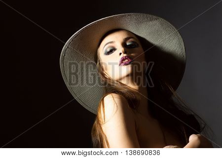 young glamour sexy woman with bright fashionable makeup on pretty face with bare shoulders and brunette hair in round retro hat posing in studio on blackbackground