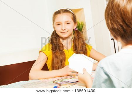 Beautiful girl playing card game sitting at the gaming table against her opponent at the room