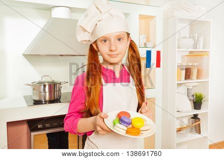 Young French baker, girl in cook's hat and apron, with plate of colored macarons at the kitchen