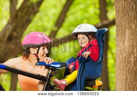Sporty mother and her toddler daughter, sitting in the bicycle seat during bicycle ride in the forest