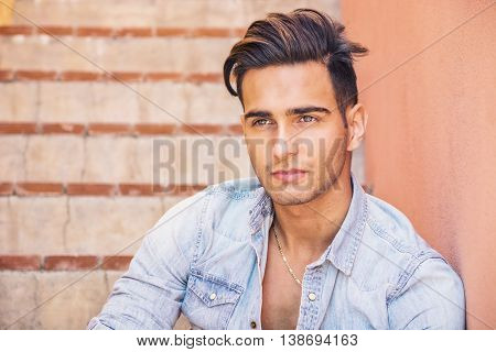 Portrait of handsome man with tattoo on arms sitting on cement stairs while leaning on wall, looking at camera
