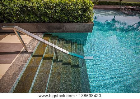 Seven stepping down stairs with stainless steel bar into water of mosaic swimming pool which reflected by tree's shadow on surface and decorated by bush.