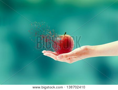 Hand holding apple in state of disintegration on blurred background