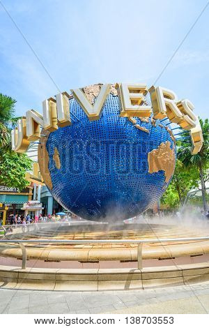 SINGAPORE - JULY 9: Tourists and theme park visitors taking pictures of the large rotating globe fountain in front of Universal Studios on JULY 9 2014 in Sentosa island Singapore