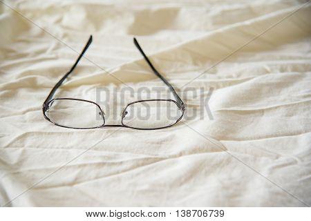 Modern Glasses on white bed in the morning sundayfor background