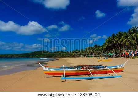 A colorful outrigger boat parked on a tropical beach in the Philippines