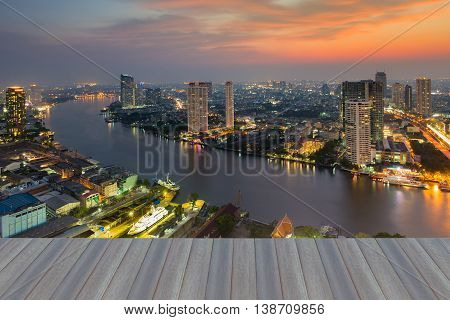 Opening wooden floor, River curved in city downtown with sunset sky background