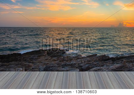 Opening wooden floor, Sunset sky over seacoast with natural rock beach