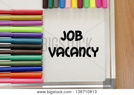 Job vacancy written on whiteboard over wooden background poster