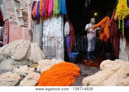 MARRAKESH - JULY 09: Unknown man dyeing fabric in a market (souk), July 09, 2013 in a Marrakesh, Morocco. The market is one of the most important attractions of the city Marrakesh, Morocco