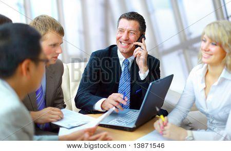 Business man spreken op de telefoon terwijl in een vergadering