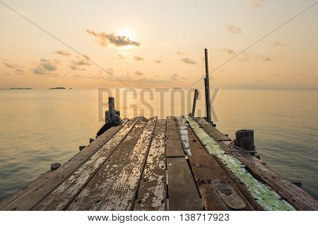 Wooden jetty bridge with tranquil scene of seascape during sunrise at Ao Lung Dam beach in Samet island Thailand.