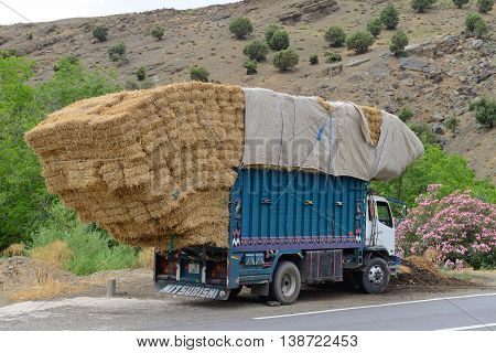 ATLAS, MOROCCO - JULY 10: Overloaded truck staying on road, July 10, 2013 in Atlas Mountains, Morocco. Road in Atlas Mountains very popular tourist route in central Morocco.