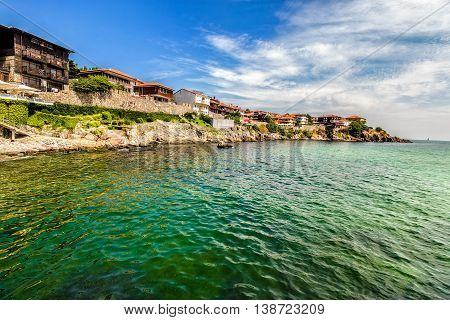 ancient city on a rocky promontory of the peninsula near the sea. sea with small waves and a trace of water bike