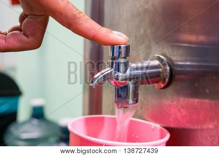 Hand holding a glass of water poured faucet.