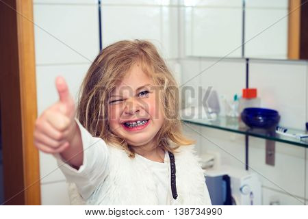 Little Funny Girl With Retainer And Thumb Up