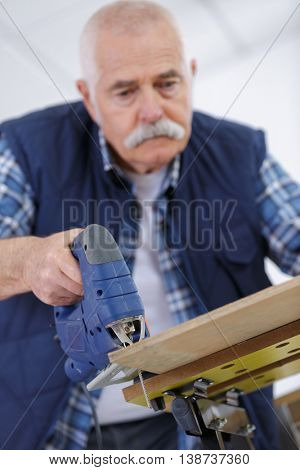 an elderly carpenter working with a band saw