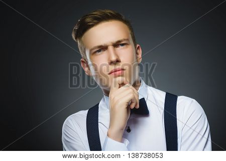 doubt, expression and people concept - boy thinking over gray background. poster