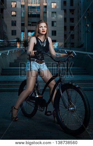Woman biker on bike rides through the city.