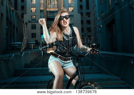 Woman with a whip in biker style on the bike she aggressive.