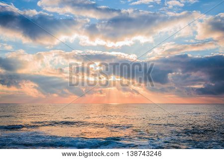 Beautiful sunrise over the sea. Sun beams break through the clouds.