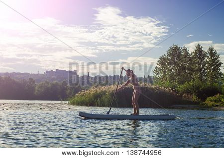 Sup Silhouette Of Young Girl Paddle Boarding At Sunset10