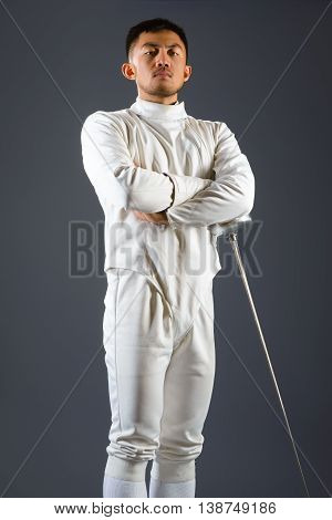 Fencing athlete posing with a sword or epee on gray background.