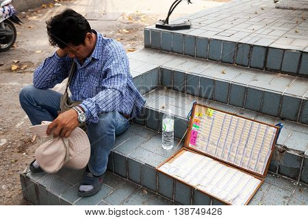 Pattaya, Thailand - March 28 2016: Tired lottery seller sitting on a street selling cheap raffle tickets
