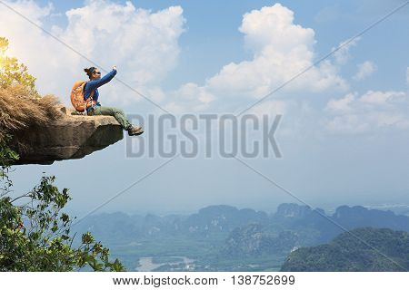 young woman backpacker taking photo with cellphone on mountain peak cliff