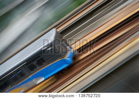 Urban Commuter Rail. An elevated commuter rail car speeds along a track. Motion blur.