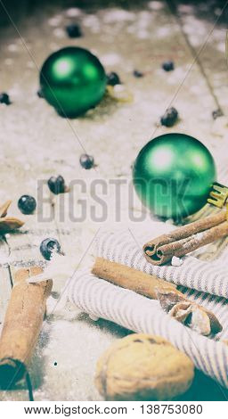 Christmas background with walnuts, cinnamon and anise on a rustic wooden table. Vintage toned photo