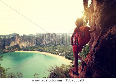 young woman backpacker enjoy the view at seaside cliff