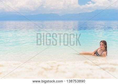 Young european woman in bikini with good mood and languishing look lies in beautiful tropical calm sea under cloudy soft sky at sunny day