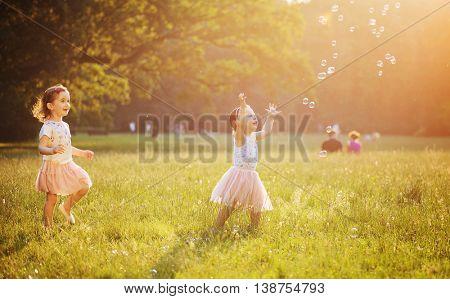 Happy little kids blowing soap bubbles in summer park