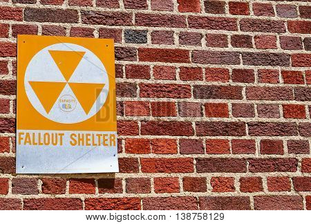 DODGE CITY, USA - MAY 17, 2015: Fallout shelter sign attached to a brick wall.